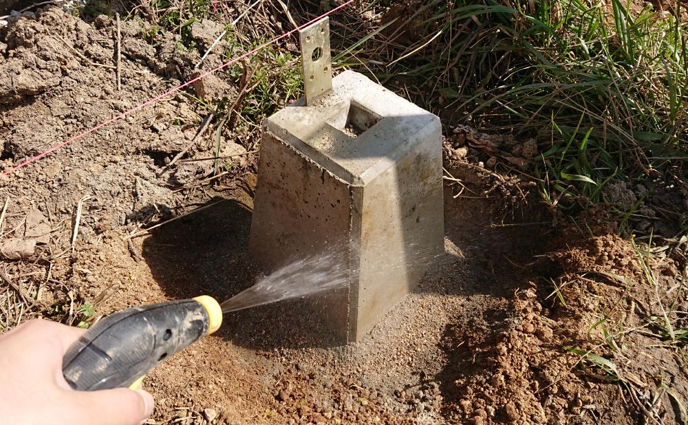 基礎穴に流し入れたドライモルタルに水を掛ける